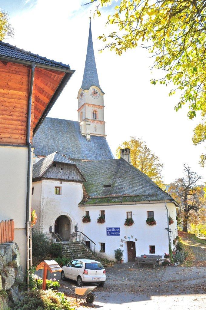Gasthof Leikam an der Kirchenburg in Hochfeistritz Nummer 28, im Hintergrund Pfarr- und Wallfahrtskirche Unsere Liebe Frau - Hochfeistritz, Kärnten (9372-KTN)