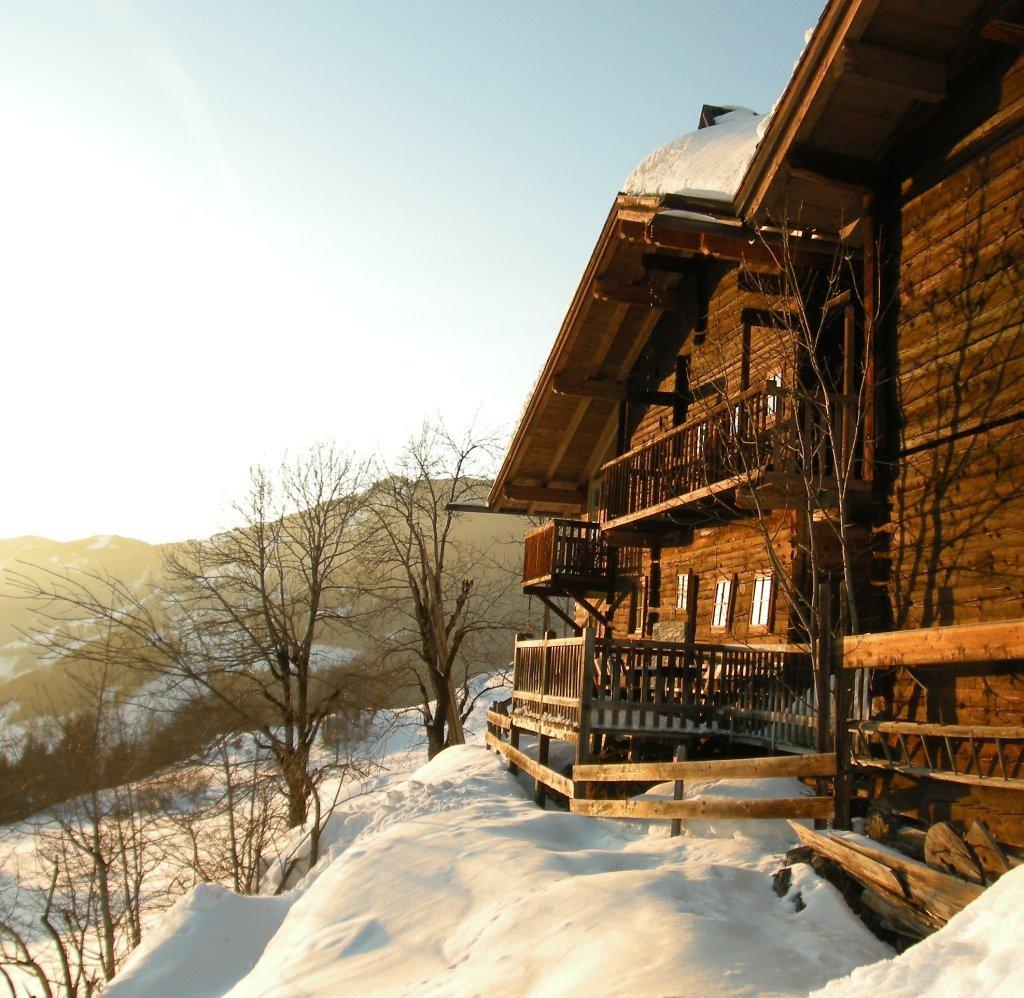 Südostansicht historisches Bauernhaus Hochrainberg mit Sonnenterrasse und Balkon in warmer Wintersonne - Oberlehen, Salzburg (5621-SBG)